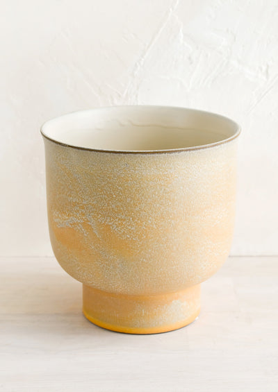 A ceramic planter with footed silhouette in mottled tan glaze.