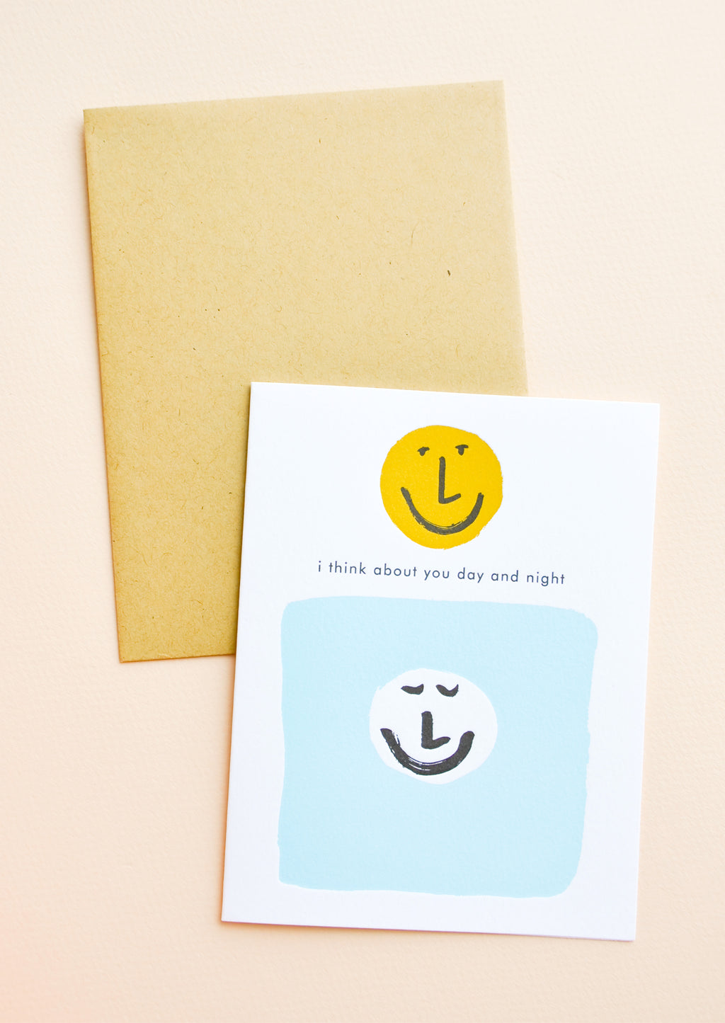 "1: White greeting card with black ""I think about you day and night"" text. Two smiley faces, one white and one yellow. Shown with brown envelope."