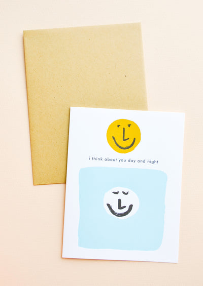 "White greeting card with black ""I think about you day and night"" text. Two smiley faces, one white and one yellow. Shown with brown envelope."