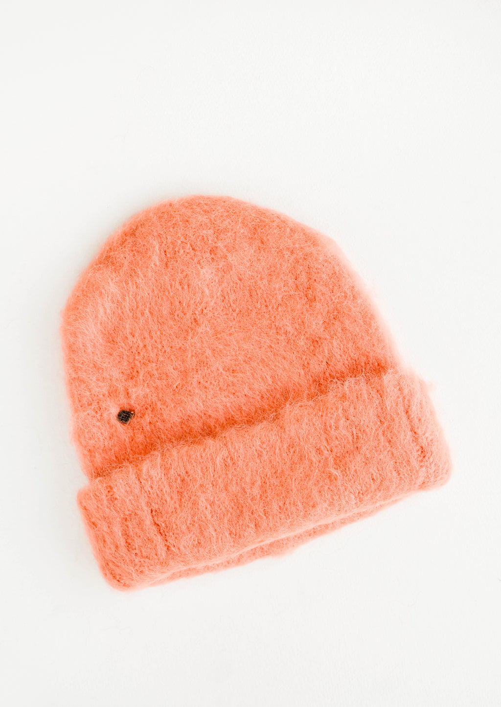 Grapefruit: Fuzzy coral pink beanie with very small metal logo just above bottom fold.