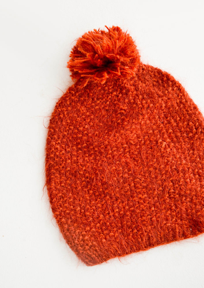 Rust: Rusty red knit beanie with pom pom on top.