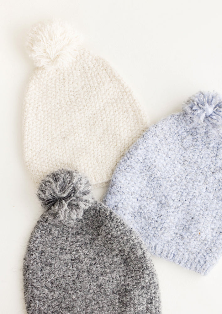 2: One cream, one blue, and one grey knit pom pom beanies laid out.