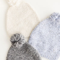 Winter White: One cream, one blue, and one grey knit pom pom beanies laid out.