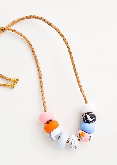 Necklace featuring colorful patterned clay beads on braided leather cord