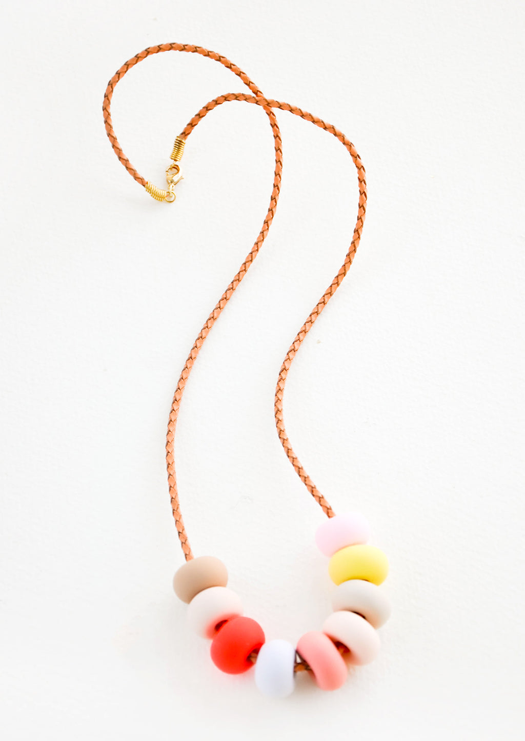 Italian Ice: Woven leather cord necklace with gold clasp and rounded clay beads tans, pinks, red, blue, and yellow.