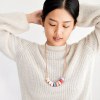 3: Model wears clay bead necklace and ivory sweater.