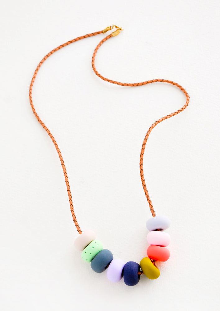 Summer Fair: Woven leather cord necklace with gold clasp and rounded clay beads red, blue, lime green and mustard yellow.