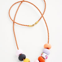 1: Necklace with light brown woven leather cord and nine clay beads in pink, navy, yellow, red, and orange.