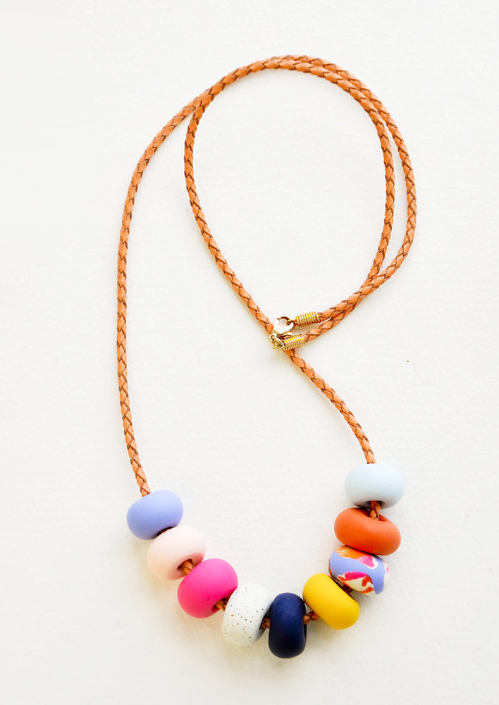 9 Bead: Necklace with gold clasp, brown woven leather cord, and nine multi-colored clay beads in blues, pinks, yellows, and oranges.