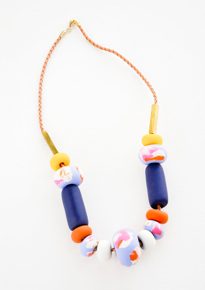 Big Bead: Necklace with gold clasp, brown woven leather cord, rectangular brass beads, and beads of varying shapes and sizes in yellows, pinks, blues, and oranges.