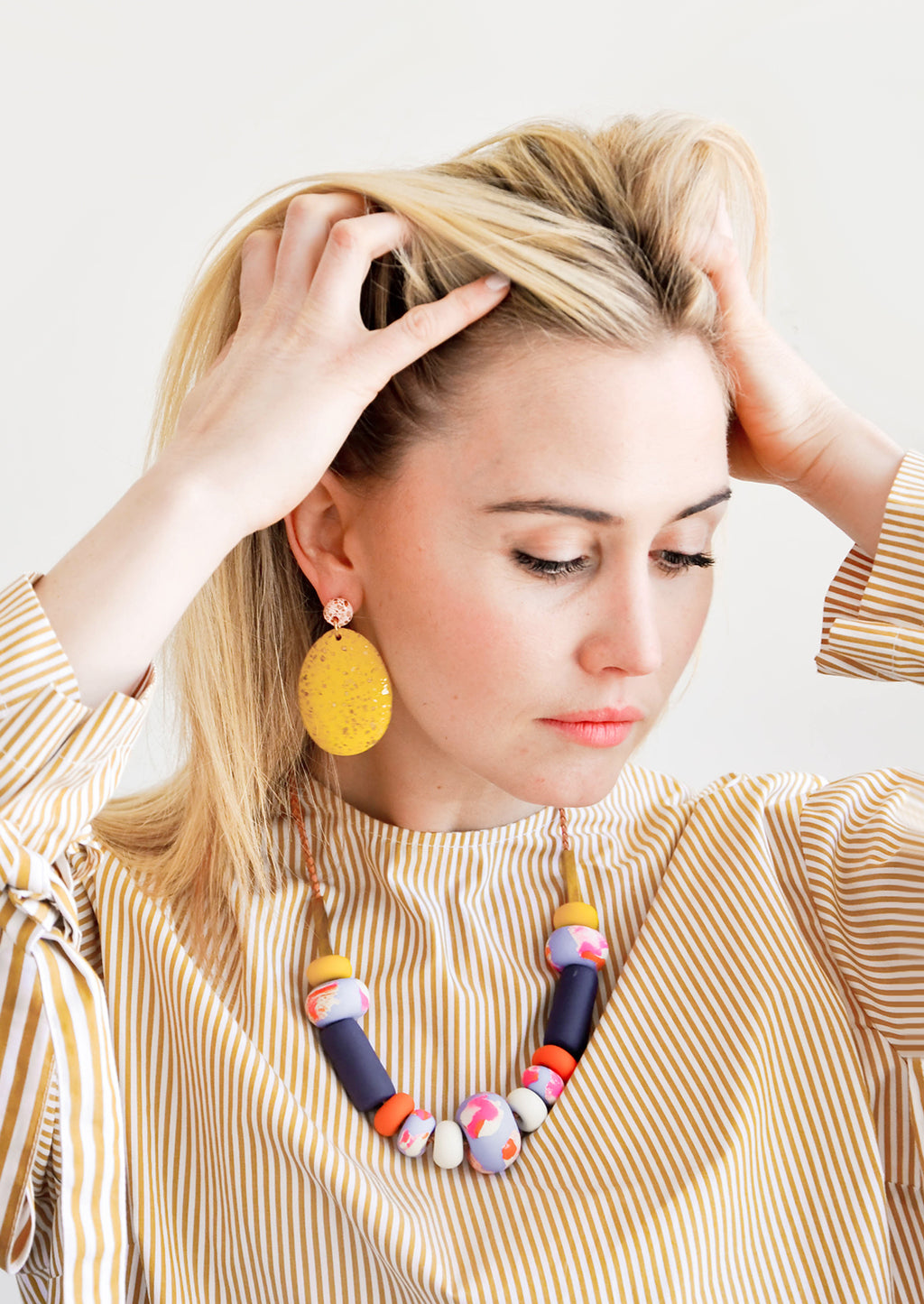 4: Model wears large yellow earrings and clay bead necklace.