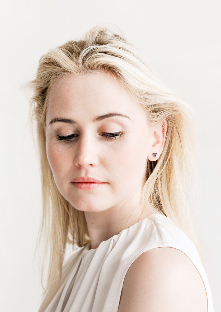 3: Model wears stud earrings and white blouse.