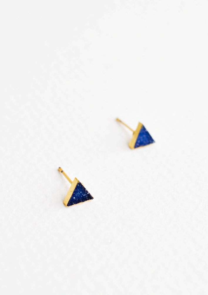 Triangular stud earrings of blue textured stones in gold setting.