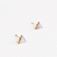 2: Triangular stud earrings of pale gray textured stone in gold setting.