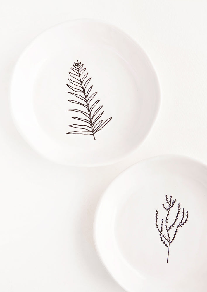 1: Two round white ceramic dishes each with a single black etched botanical image.