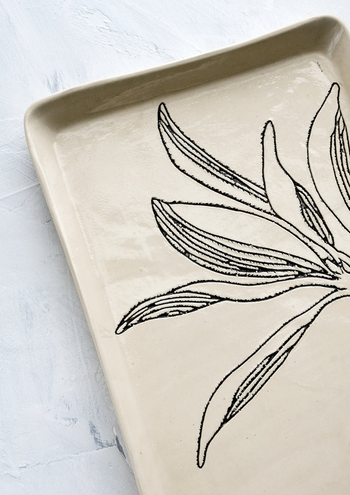 7: Black etched botanical detailing on a ceramic tray.