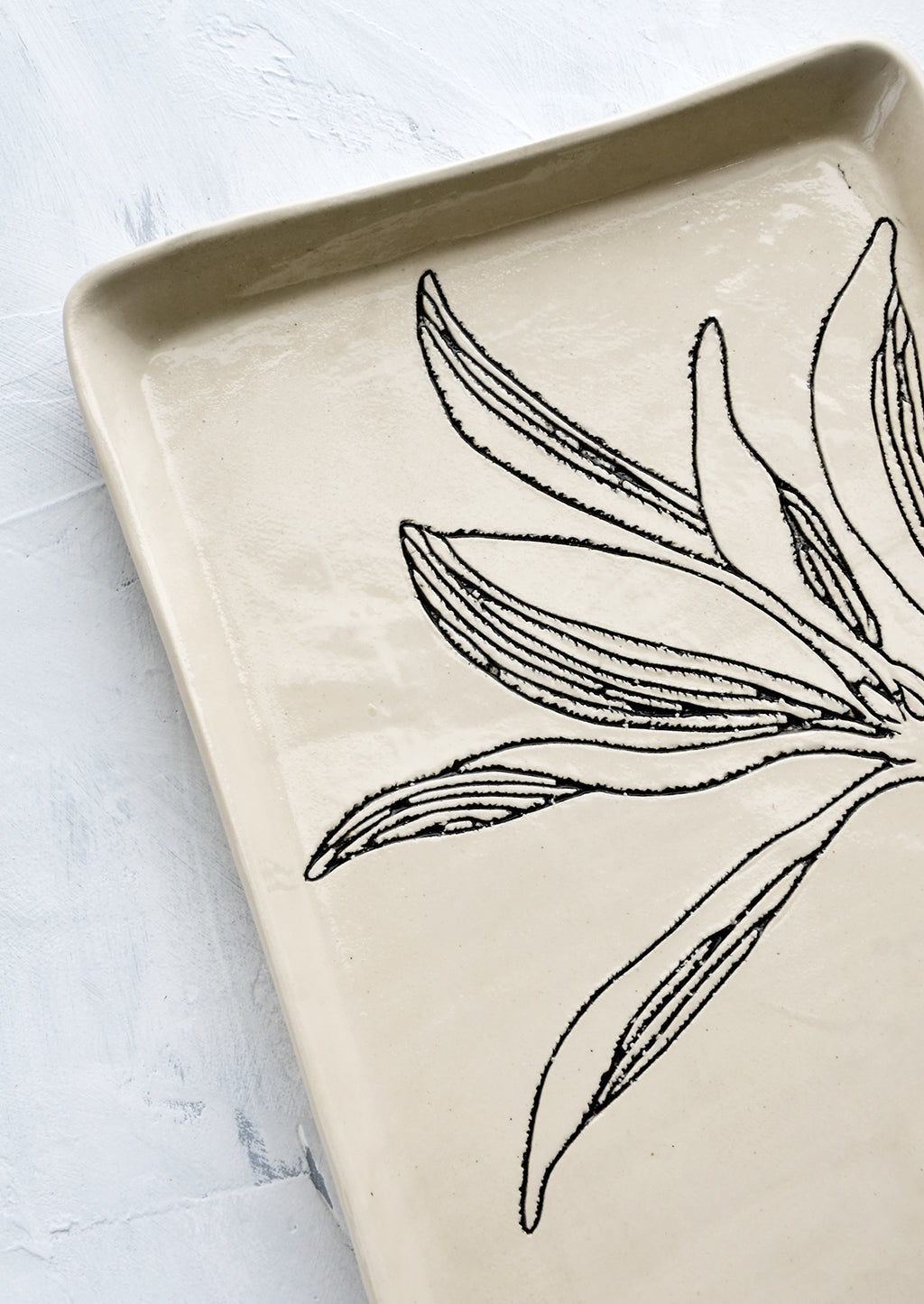 5: Black etched botanical detailing on a ceramic tray.