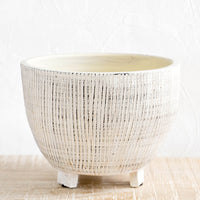 1: Round ceramic planter with tripod footed base. Allover ribbed texture with distressed black detail.
