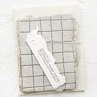 1: Packaged set of cards made from handmade paper with a letterpress printed grid pattern.