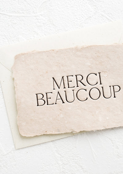 "A greeting card made from blush handmade paper and large letters spelling ""Merci Beaucoup""."
