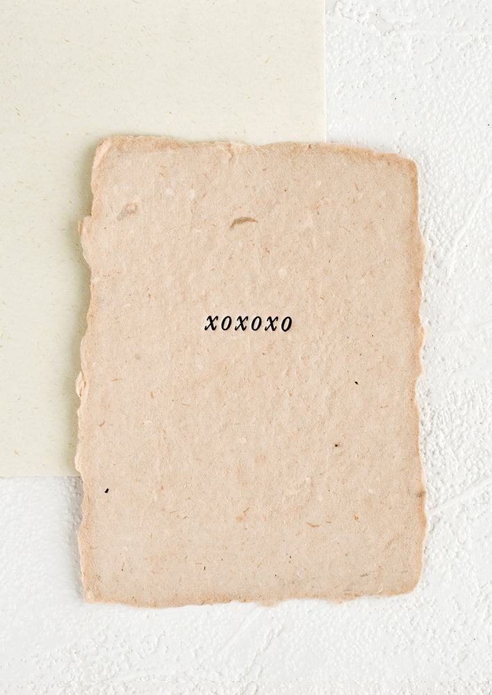 "1: A greeting card made from pink handmade paper with ""xoxoxo"" printed on front."