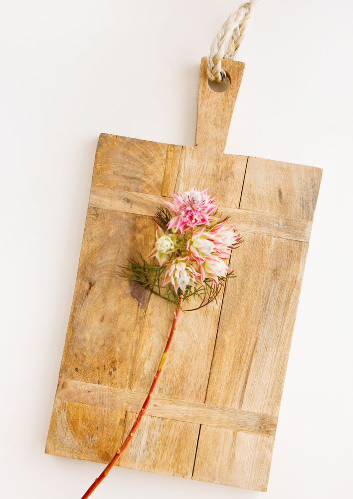 1: Rectangular wooden cutting board with rustic look, displayed with flowers.