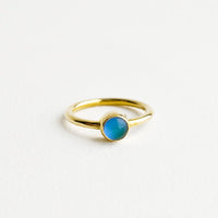1: A gold ring with a round blue stone.