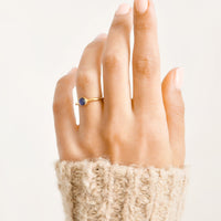 2: A woman's hand with a blue stone ring on her ring finger.