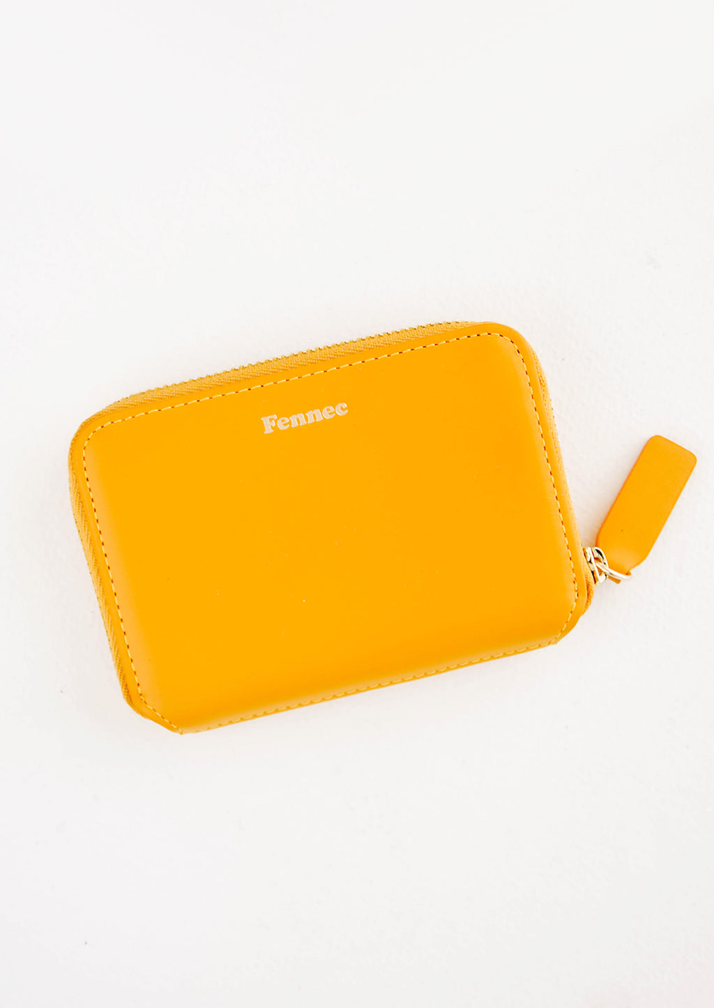 Mandarin: Small orange leather zip wallet with Fennec embossed in small gold letters at top of wallet face.
