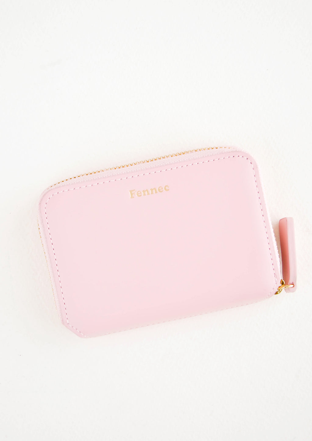 Pale Pink: Pale pink leather zip wallet with brand name Fennec embossed in small gold letters at top center of wallet face.