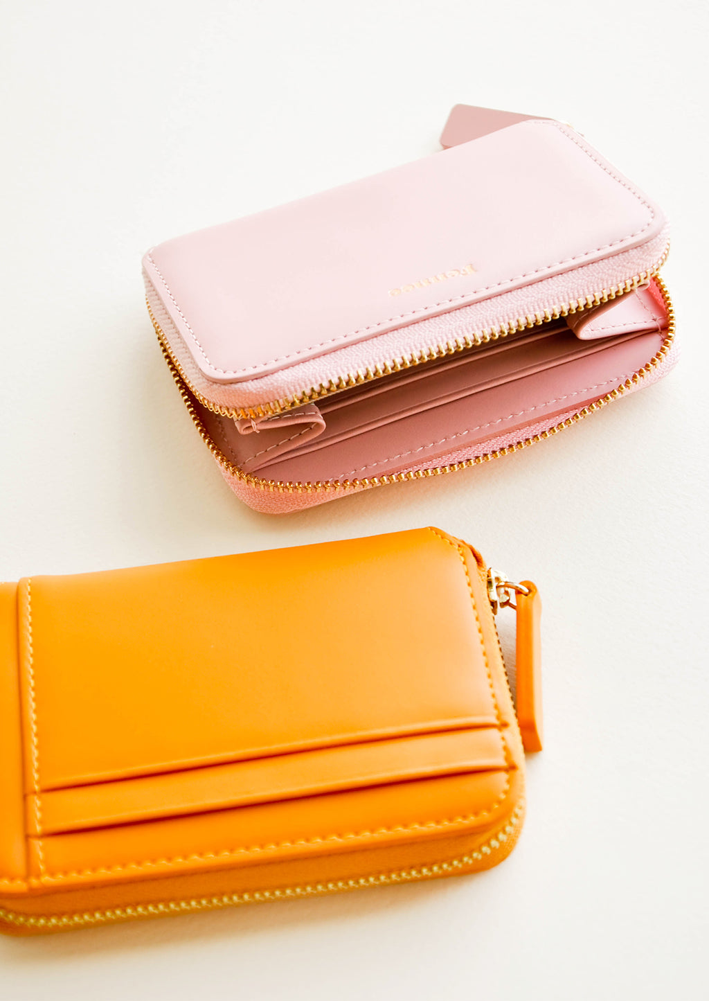 4: Pale pink leather wallet shown unzipped next to orange wallet with three exterior card slots.