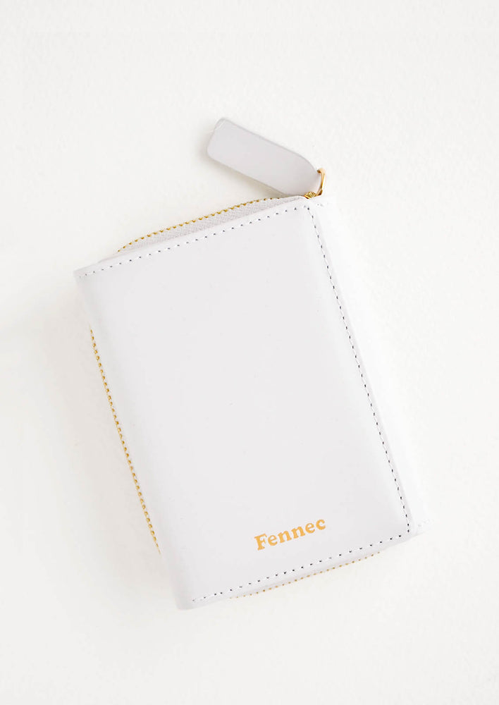 Cloudy: Light grey leather wallet that zips on three sides, in a closed position, with matching tab pull.
