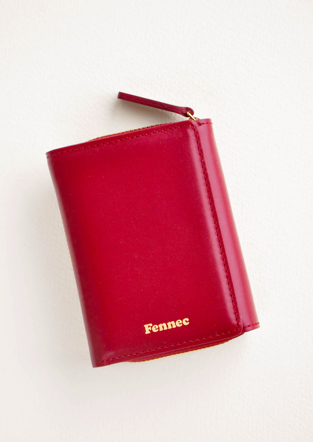 Marsala: Dark red leather wallet that zips on three sides, in a closed position, with matching tab pull.