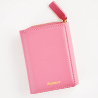 Rose: Rose red leather wallet that zips on three sides, in a closed position, with matching tab pull.