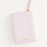 Violet: Violet leather wallet that zips on three sides, in a closed position, with matching tab pull.