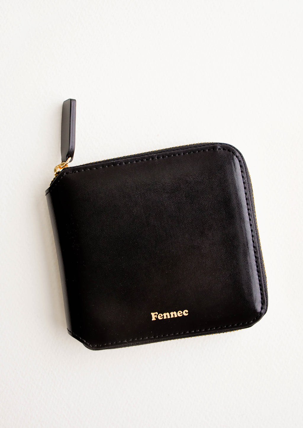 Black: Black leather wallet that zips on three sides, with matching tab pull.