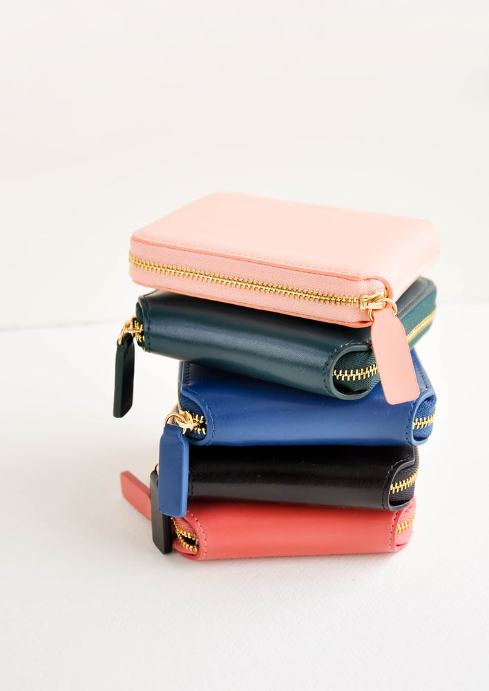 9: Product show showing multiple colors of zip wallet in a stack.