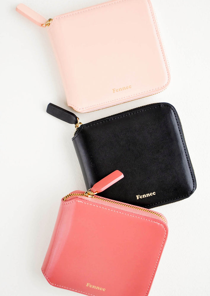 1: Three leather zip wallets in pale pink, black, and deep pink.