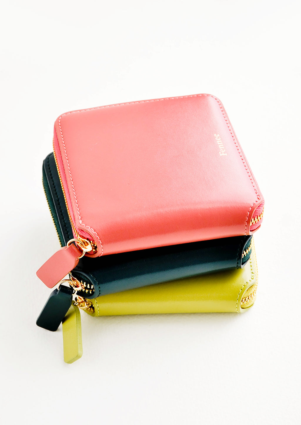 3: Product show showing multiple colors of zip wallets in a stack.