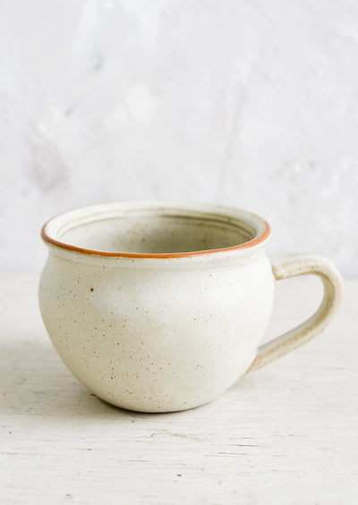 A beige ceramic mug with light speckling in a rounded shape with a handlle.