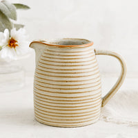 1: A tan ceramic pitcher with striped texture.