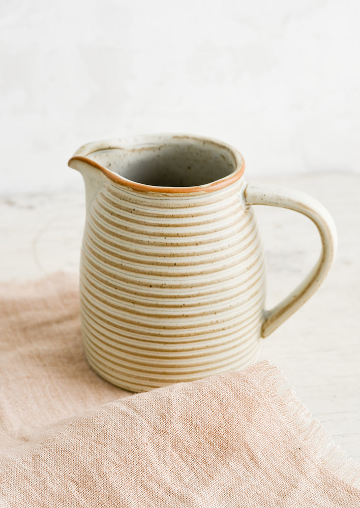 3: A tan ceramic pitcher with striped texture on top of pink linen.