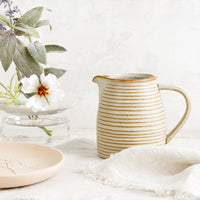 2: A tan ceramic pitcher with striped texture.