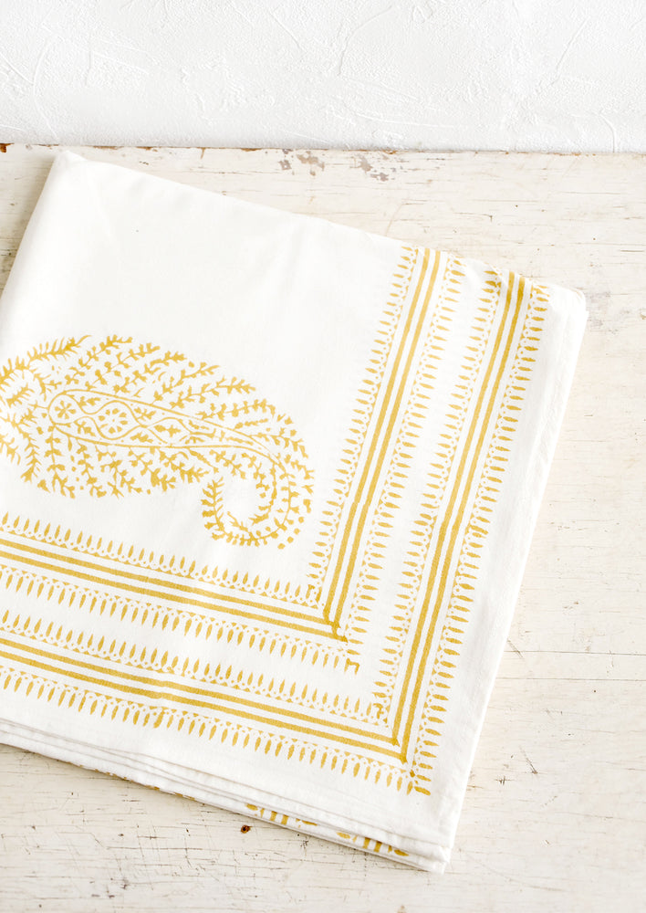 Folded white cotton tablecloth with mustard paisley pattern