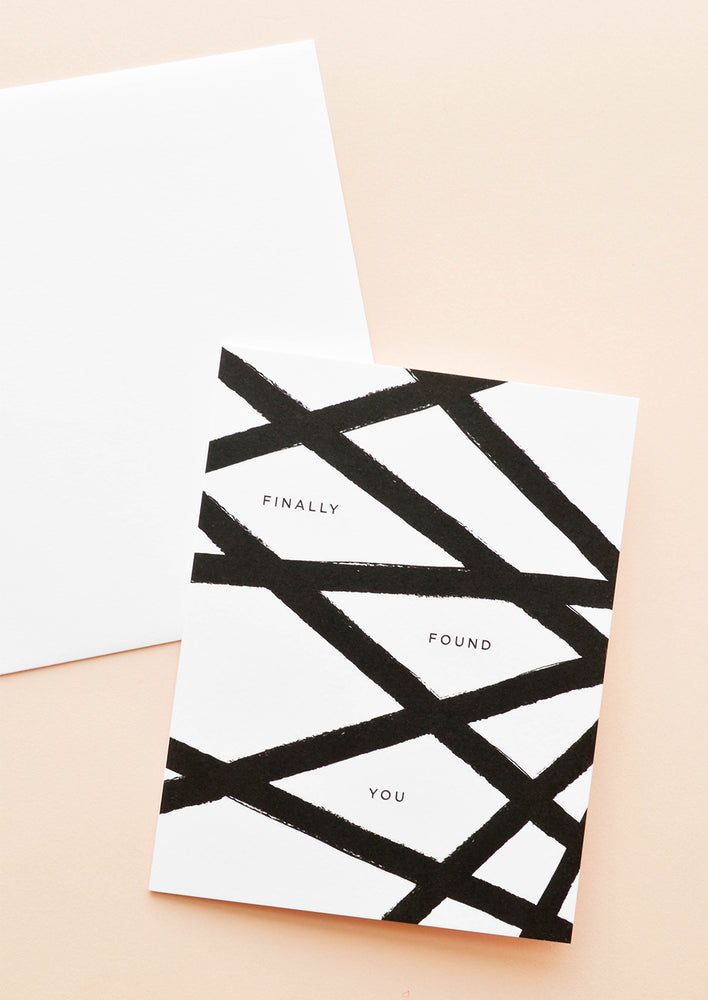 "1: White greeting card patterned with a web of black lines and the words ""finally found you"" in black text."