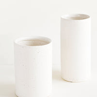 3: Vases made from white, textured concrete-like material in two different sizes, short and tall