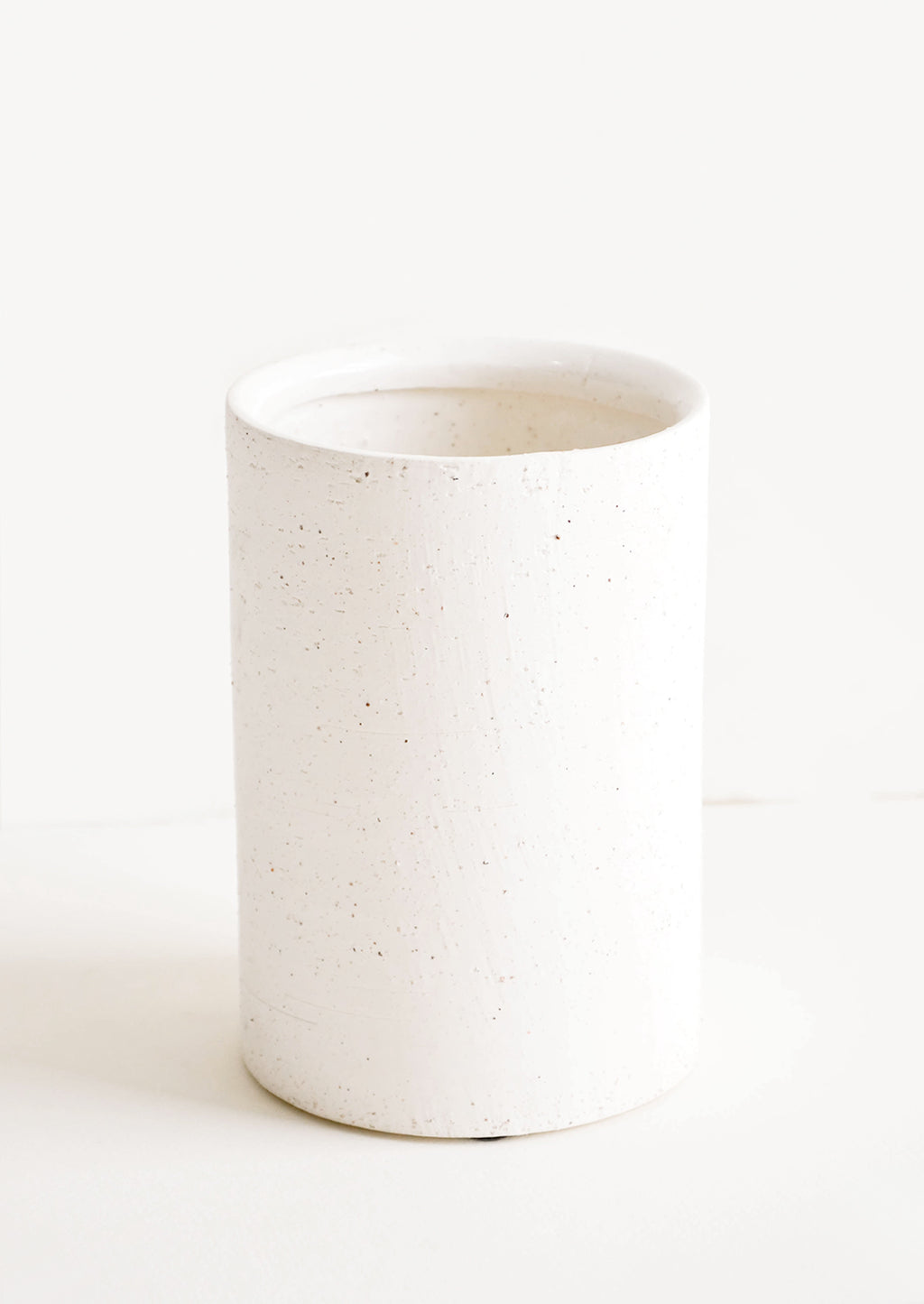 Wide [$28.00]: Vase in short and wide silhouette made from textured, concrete-like material in white