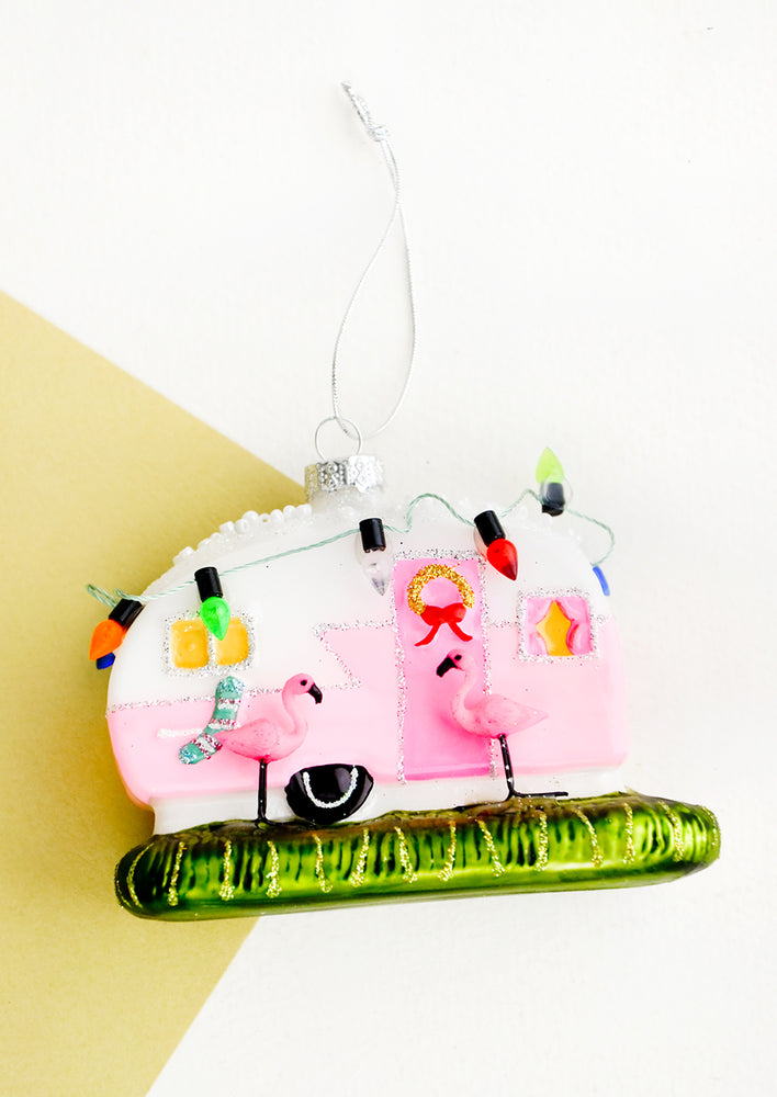 1: A glass ornament in the shape of an RV decorated for Christmas with two flamingos out front.
