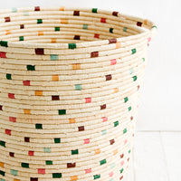1: A round raffia hamper in natural with colorful dashes throughout.