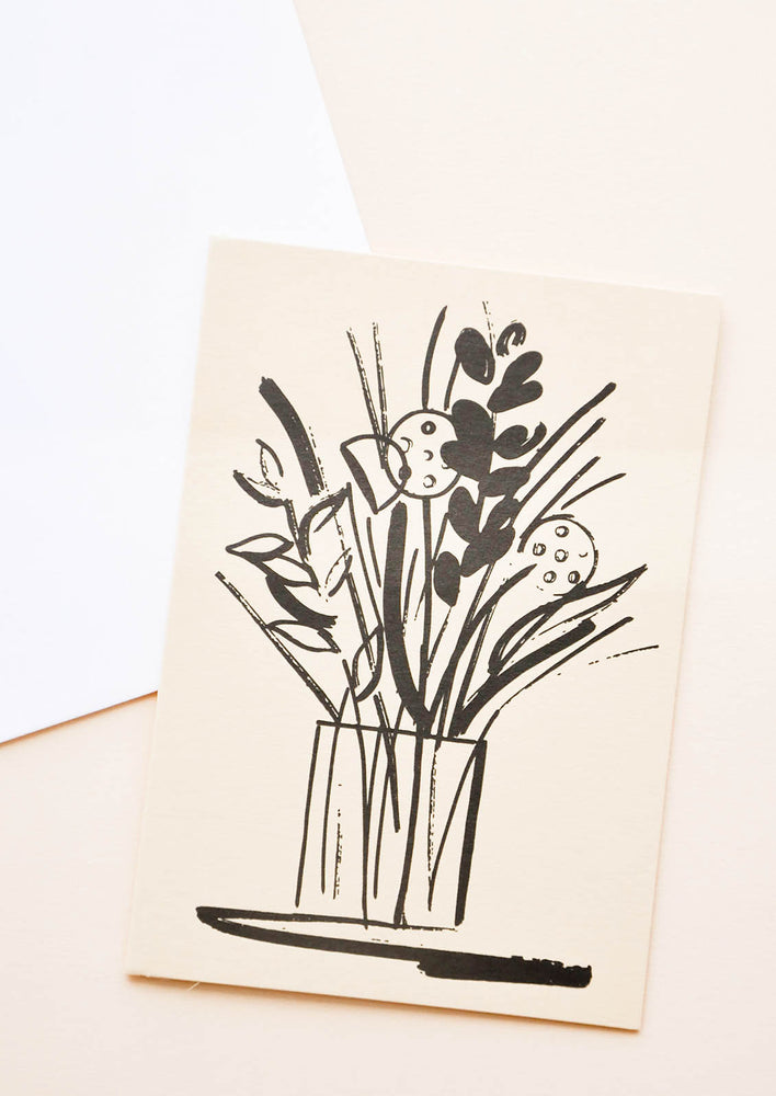 1: A white envelope and tan greeting card featuring an illustrated floral arrangement in black.